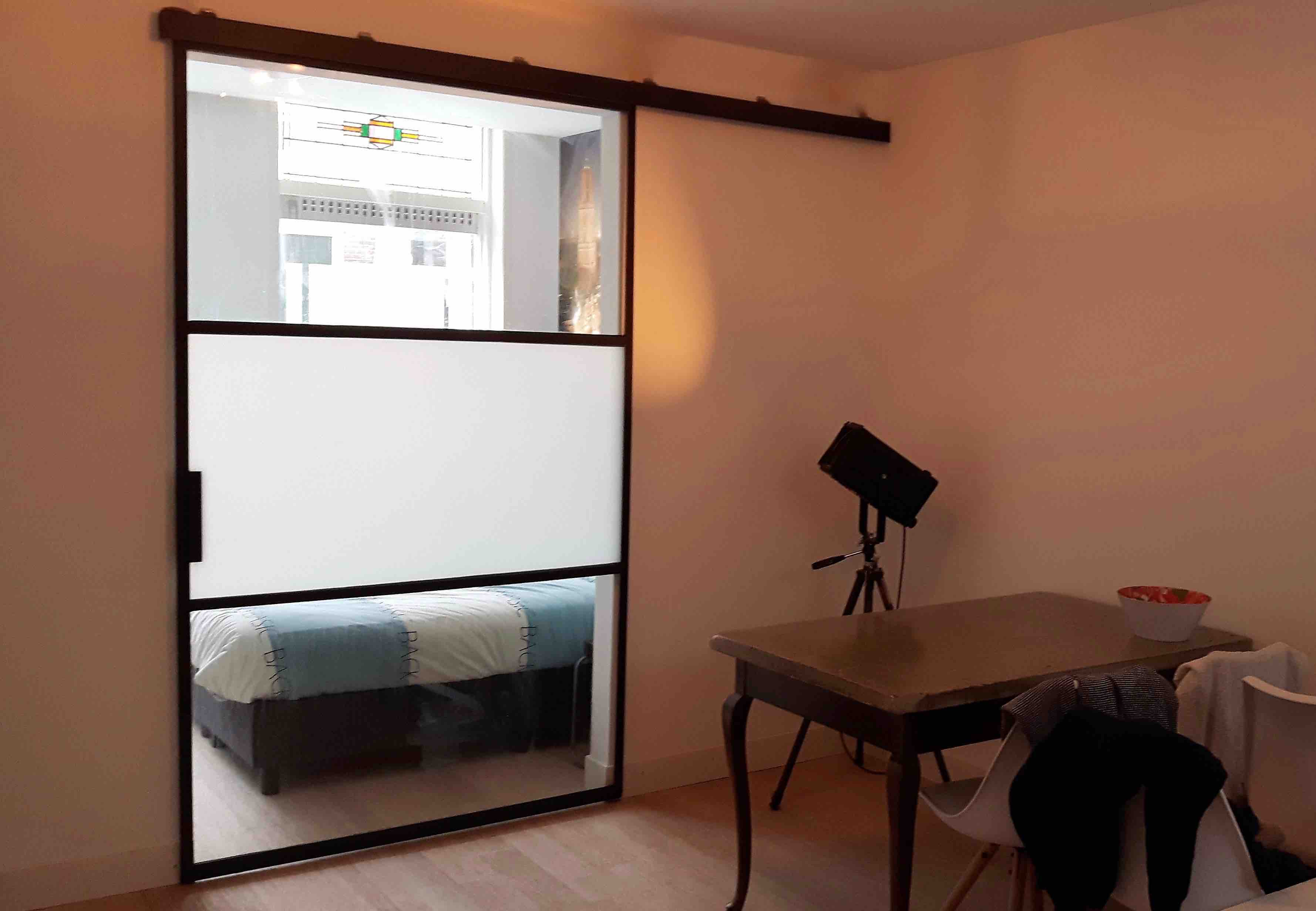 Voorbeeld stalen schuifdeur (extra breed) met 3 vlakken waarvan 1 vlak met gematteerd glas. Als room divider tussen woonkamer en slaapkamer.