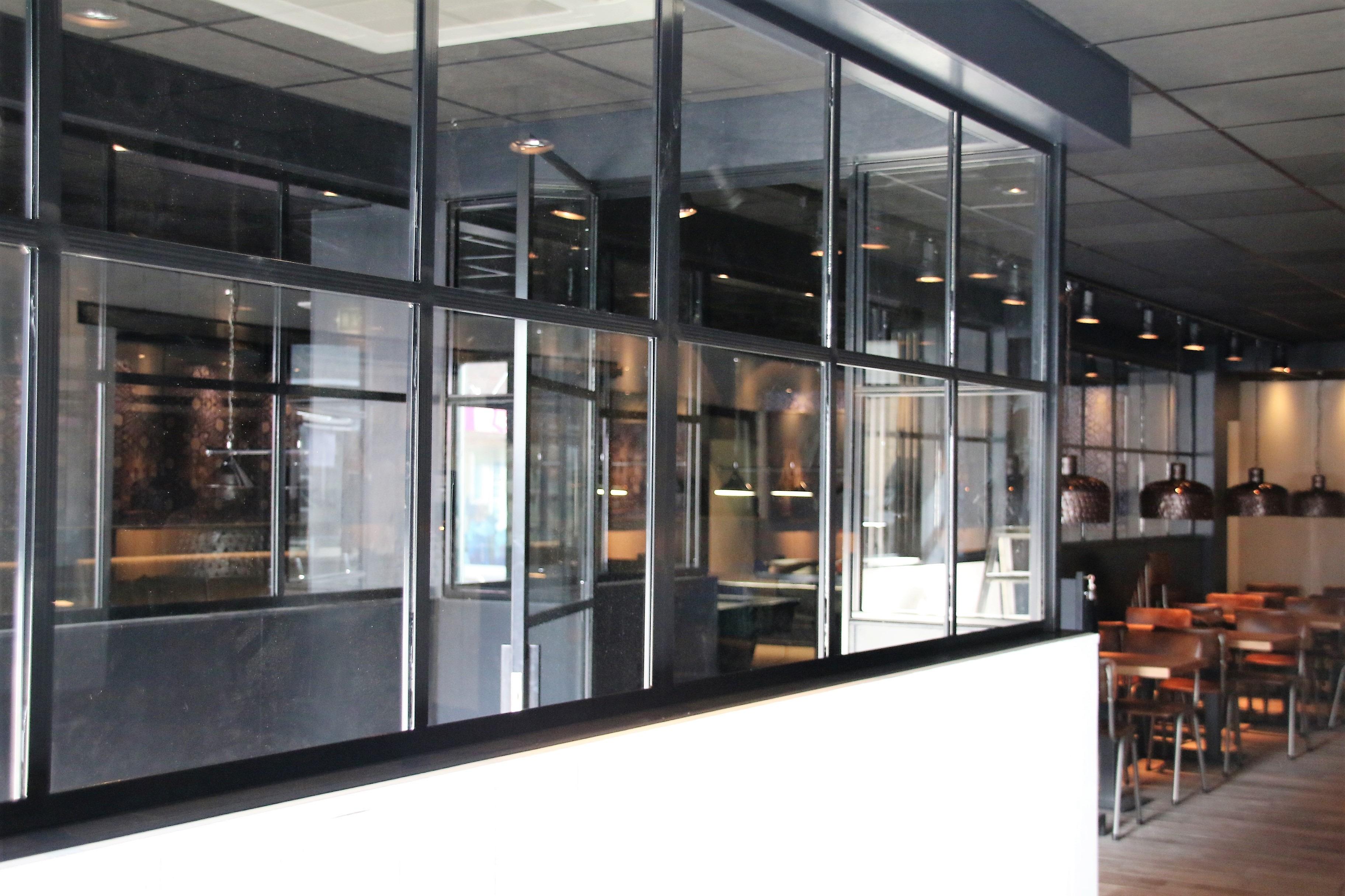 Voorbeeld van een stalen deur (scharnier) met 4 vlakken, hoekgreep en zijpanelen in Zevenhuizen.